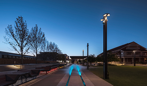 The site includes an Anzac memorial and open space with ceremonial rail line, artworks, shade structures, custom seating, water misting and feature lighting surrounded by the historic workshop buildings and new development sites including a future hotel.