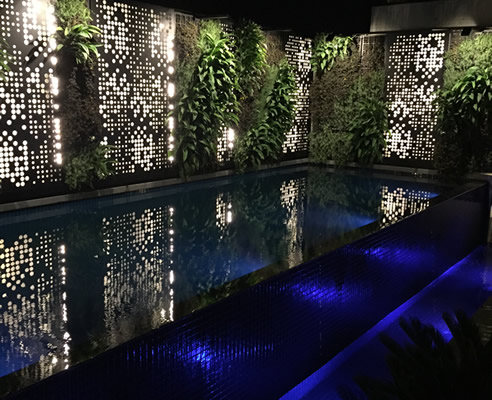backlit screens and green wall pool surround